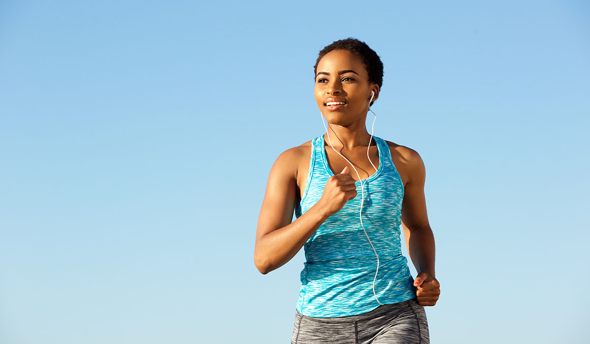 Happy Young Fitness Woman Running With Earphones