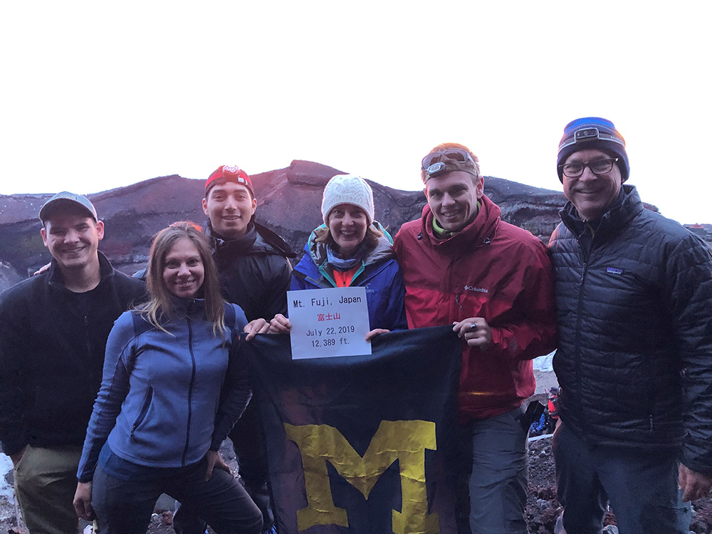 UM-Dearborn alumni greet the sun as it rises over the summit of Mount Fuji in Japan. From left to right are Andrew Kubinski, '15, MS'19; Holly Stefanski, '10, MS'14; Adrian Andrade, '17; Michele Adams, '82; Tim Brehmer, '15; and Joe Adams, '82.