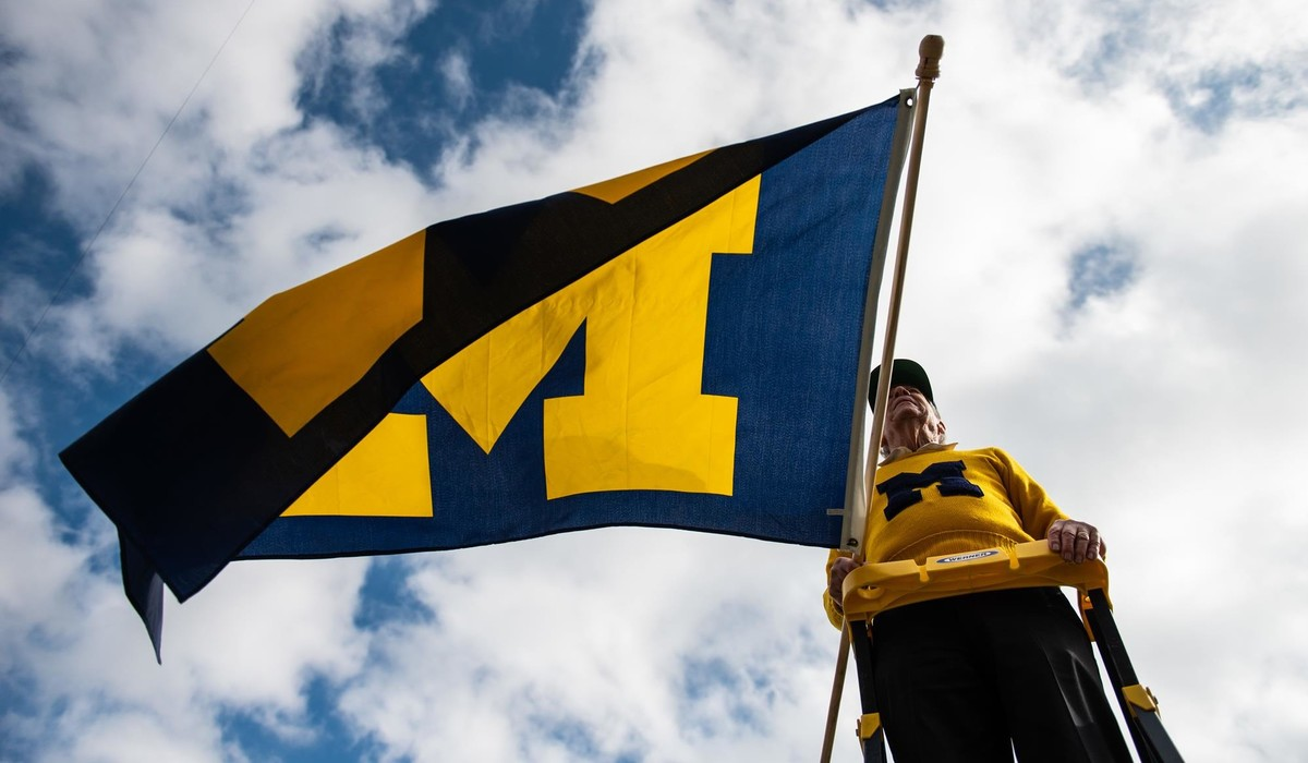 Michigan alumni cheerleader holding University of Michigan flag