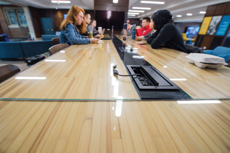 """STILL OUR UNION: The storied Billiards Room underwent a radical transformation, becoming a drop-in, coworking space that forms the core of the IdeaHub, but the Union's century of history remains ever-present, even here. The wooden tabletops, for example, are repurposed lanes from a long-disused bowling alley that mid-20th century classes might remember from their own undergraduate years. And, despite the facelift, the Union remains ultimately recognizable. """"You walk in and you'll still know this is our old Union,"""" Wibbelman says. """"It's just that it's been updated to serve our needs better today."""""""