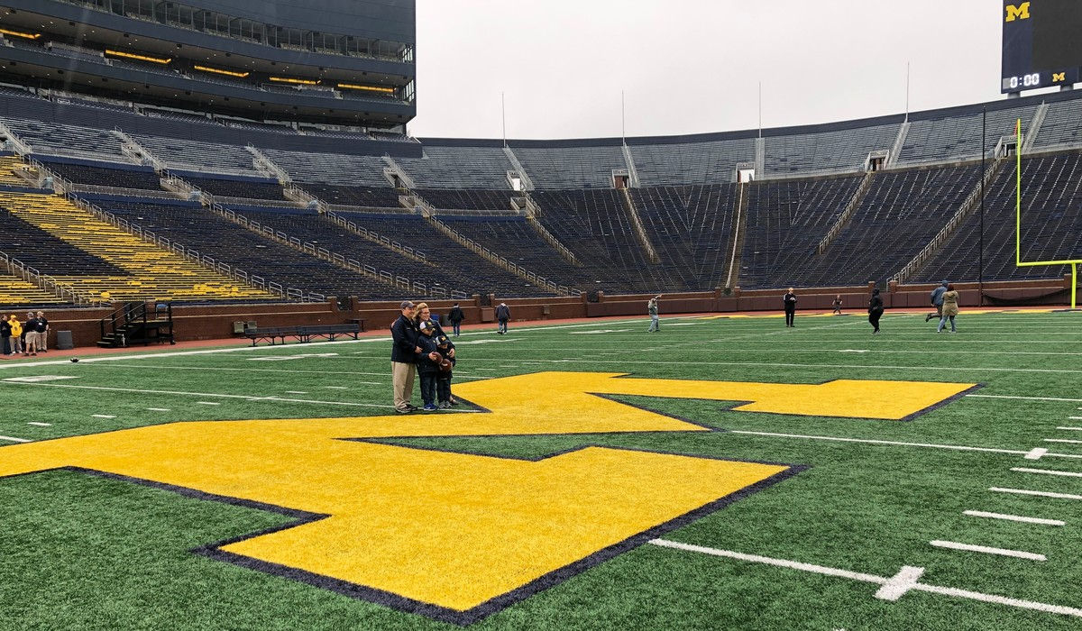 Fans take a photo at the 50-yard line of Michigan Stadium during a Big House Tour
