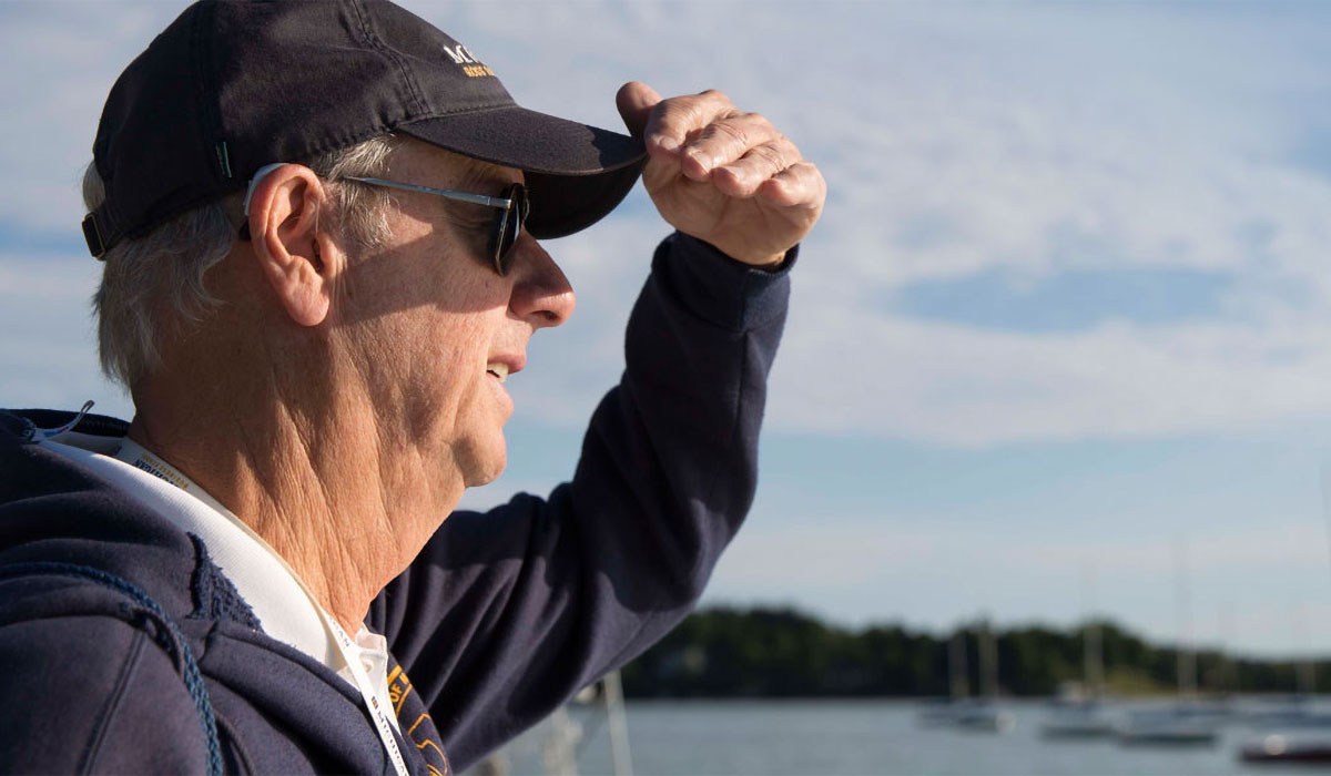 Man looking out at sailboats on Walloon Lake at Camp Michigania