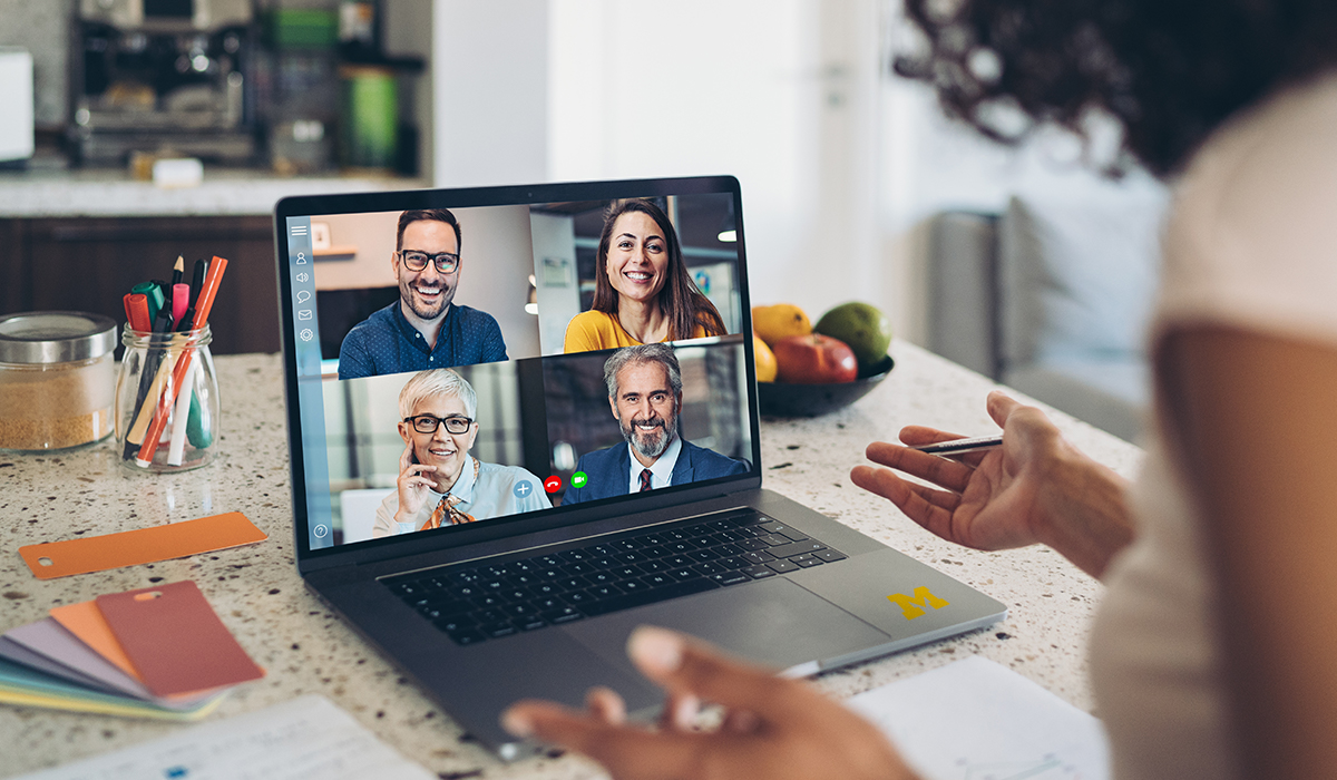 Woman video-chatting with four people on a computer