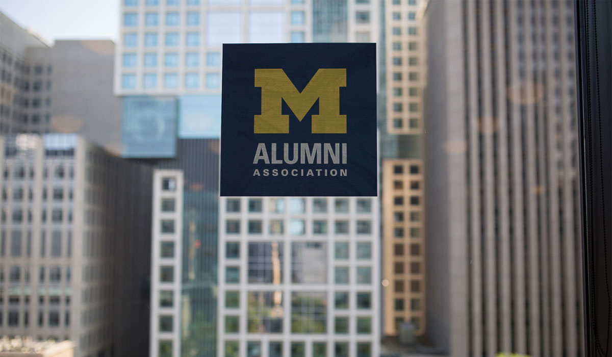 Alumni Association logo decal on a window with buildings in the background