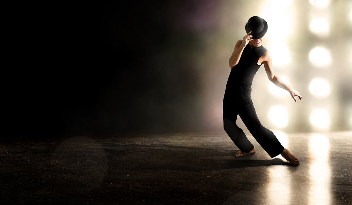 Male dances against backlighting with derby hat.