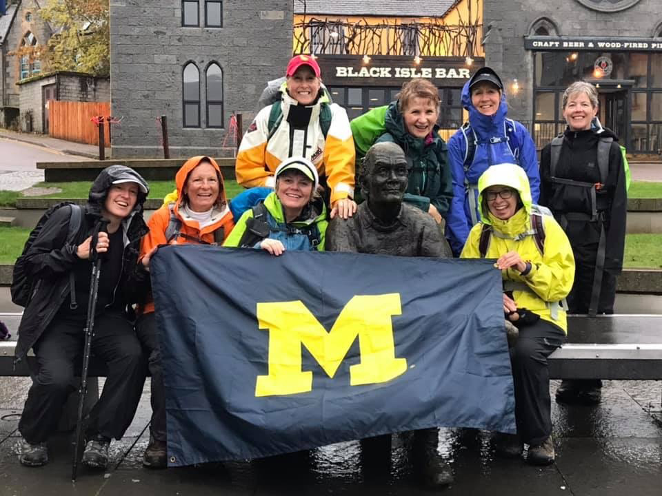 """Alumnae pose with the Block M and the """"Man with the Sore Feet"""" at the end of their eight day, 100-mile walk of the West Highland Way in Scotland. Pictured are: Jennifer Day, MS'10; Karla Olson-Bellfi, '82; Jan Fisher, MSW'75; Nancy Janz Clark, '69, MS'72, PhD'86; Michele Madden, '66, MA'72; Chris Black, '71, MALS'74; Debbie Ternes, '78; and Sharon Watling, PHARMD'87."""
