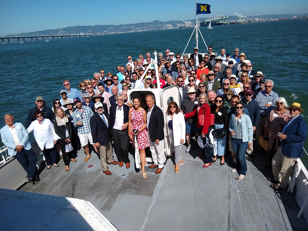 William L. Diefenbach, '72, (center, in white pants) celebrated his 70th birthday with his daughter, Christina (left of William), and 120 friends aboard the historic USS Potomac presidential yacht in San Francisco Bay. The U-M flag above them was one of three raised on the ship that day.