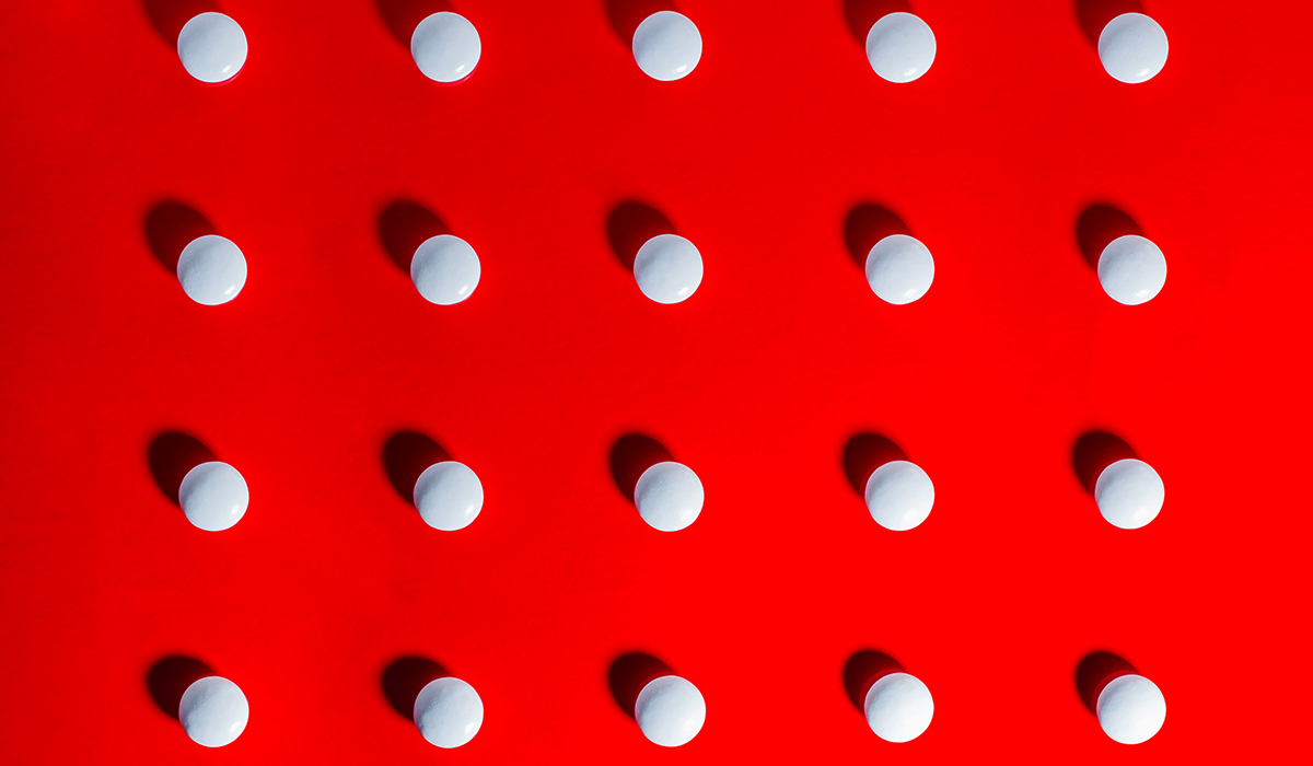 White Pills Against Red Background