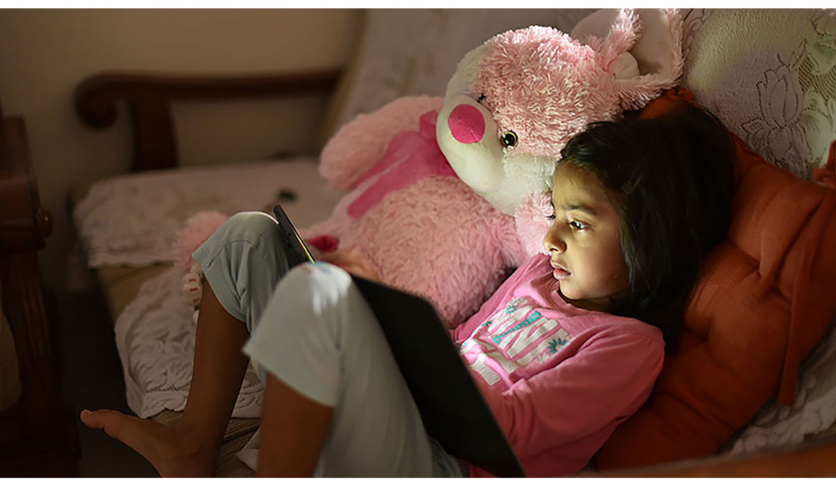 Young Girl Using Digital Tablet Along With Her Soft Toy