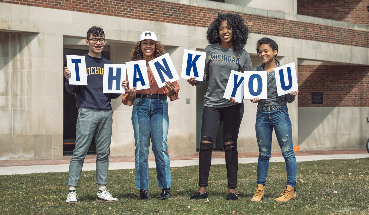 "LEAD Scholars hold a ""Thank You"" sign outside the Alumni Center at the University of Michigan"