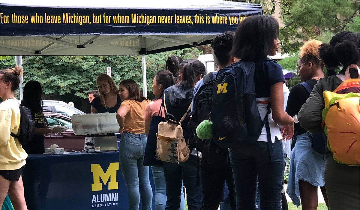Students outside an Alumni Association tent at the University of Michigan