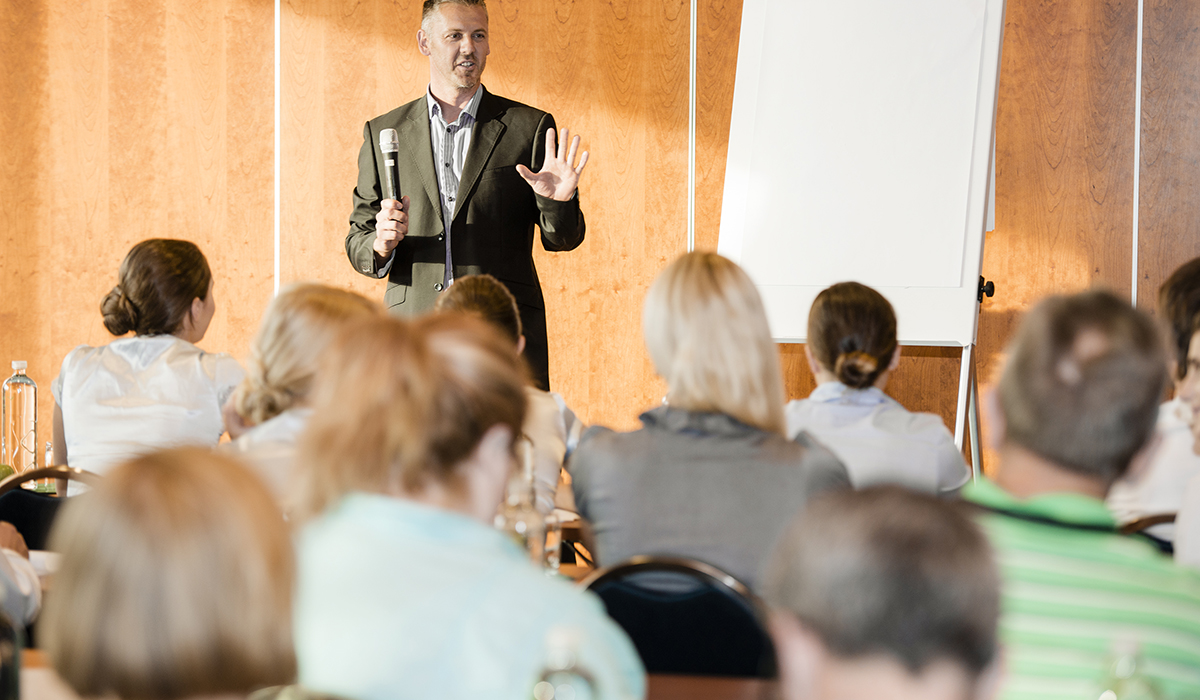 Presenter With Microphone At Business Seminar