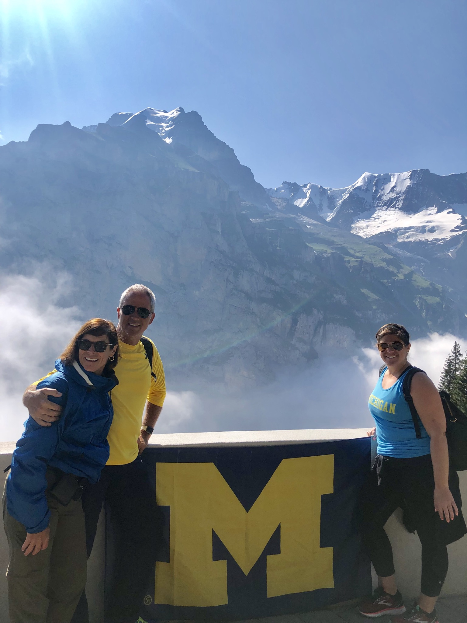 The Johnson clan of, from left to right, Kathy, '81; David, '83, DDS'85; and Stephanie, '13, MS'16, took U-M pride to the mountains of Mürren, Switzerland.