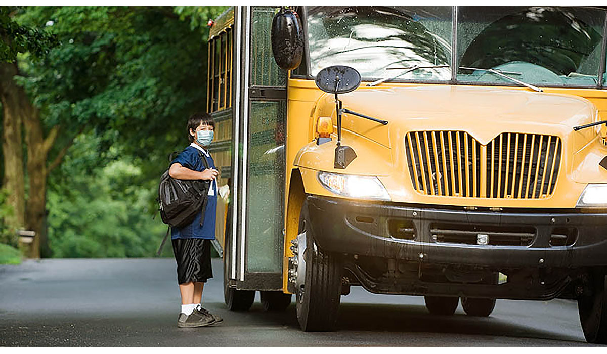 Boy With Mask Getting On School Bus