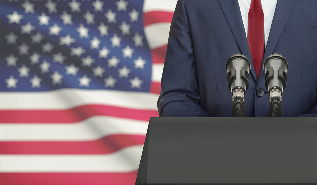 Businessman Or Politician Making Speech From Behind A Pulpit With National Flag On Background United States