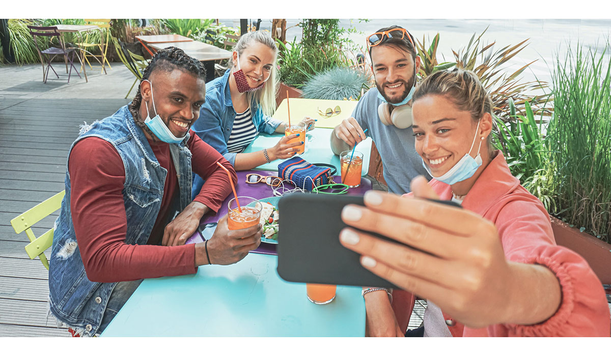 Friends Takeing Selfie In A Bar Restaurant With Face Mask On In Coronavirus Time Young People Having Fun With Drinks And Snacks Outside With New Rules After Virus Break