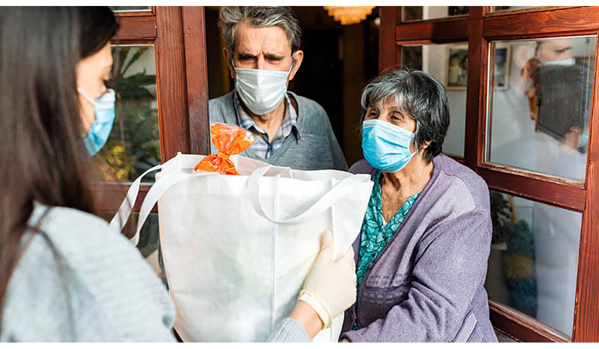 Person Delivering Groceries To Elderly Couple Gatewayextension