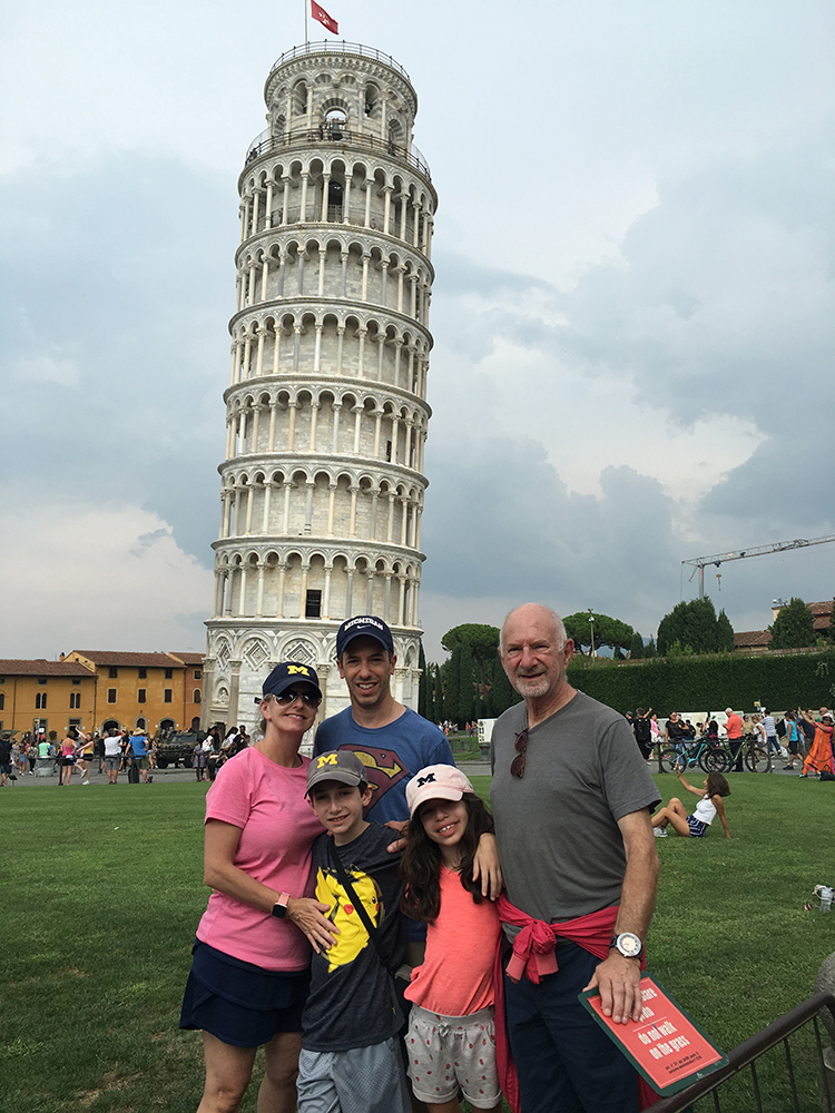 Barry Waldman, '93, verified that Italy's Tower of Pisa definitely leans with his wife, Elain, children David and Rebecca, and father-in-law Leslie. The family drove across Italy, France, and England proudly displaying the Maize and Blue.